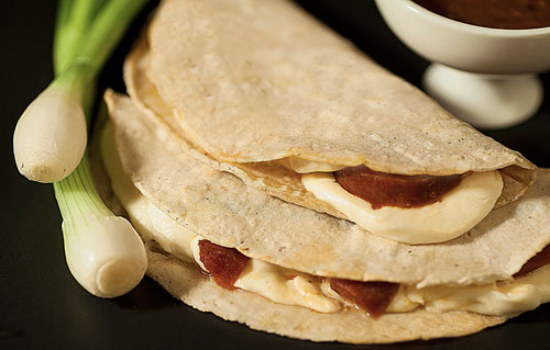 Chorizo Quesadilla next to a spring onion and salsa